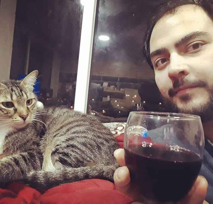 90 Day Fiance's Adam the translator poses with Oliver the cat