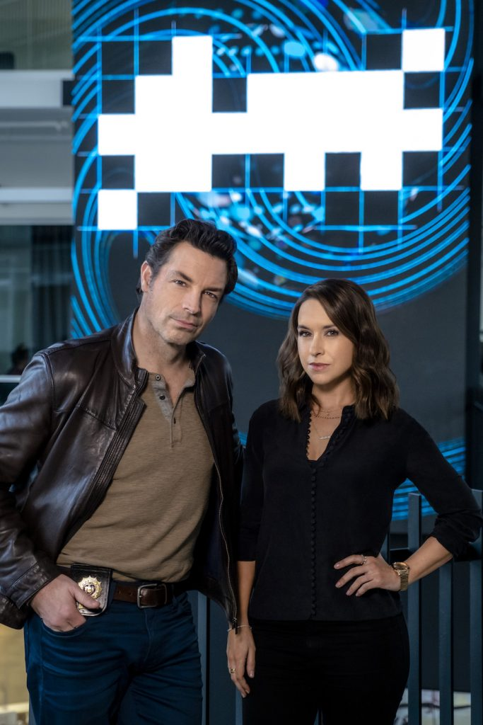 Hallmark, After volunteering to participate in a crossword solving competition with a new supercomputer, crossword puzzle editor Tess Harper finds herself swept into the investigation of the bizarre murder of a tech CEO. Photo: Brennan Elliott, Lacey Chabert Credit: ©2021 Crown Media United States LLC/Photographer:Allister Foster